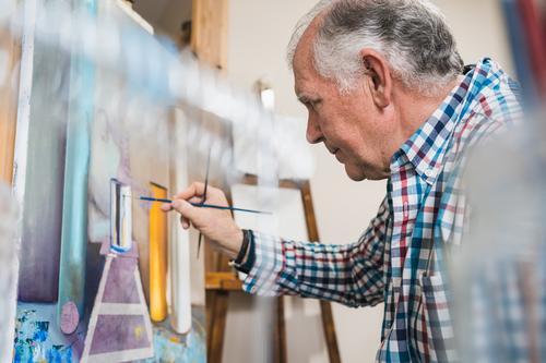 Älterer Mann malt Bild mit Pinsel Künstler gealtert Pinselblume Kunst heimwärts Inspiration zeichnen Farbe Konzentration Palette Erdöl Staffelei Papier Atelier