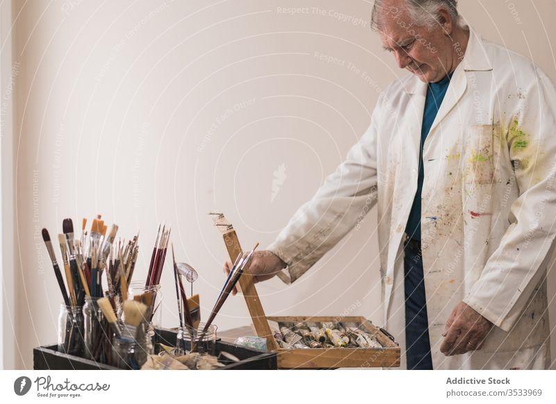 Senior-Künstlerin steht in Heimwerkstatt und wählt Farben Mann gealtert Kulisse Pinselblume heimwärts Kunst wählen Konzentration Atelier Hobby Werkstatt Empore