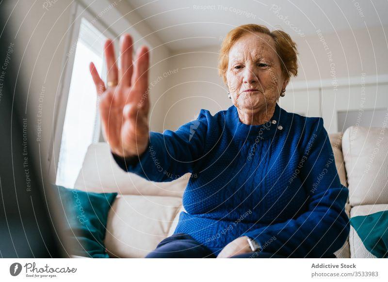 Ältere Frau kommuniziert mit einem Freund während eines Video-Chats am Laptop Videoanruf heimwärts Senior Sitzung benutzend online Gruß Lächeln abgelegen