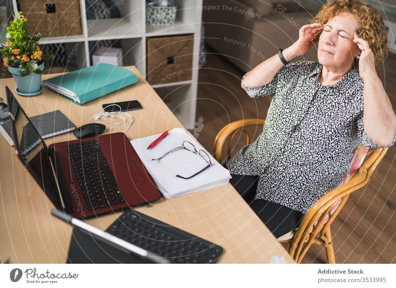 Weibliche Freiberuflerin hat Pause während der Arbeit mit Dokumenten und Geräten zu Hause Frau ruhen Kopfschmerzen müde abgelegen Entfernung Tempel reiben Stuhl