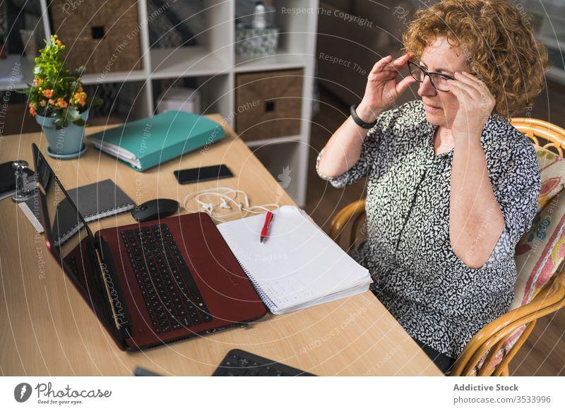 Nachdenkliche erwachsene Frau, die Musik über Kopfhörer hört, während sie zu Hause am Laptop arbeitet ruhen heimwärts Entfernung Arbeit abgelegen Pause genießen