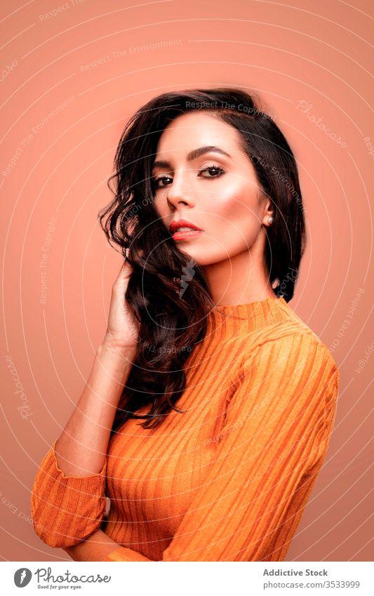Sinnliches weibliches Modell im orangefarbenen Outfit Frau Stil selbstbewusst sinnlich Farbe hell lebhaft jung trendy lässig farbenfroh Dame schön Schönheit