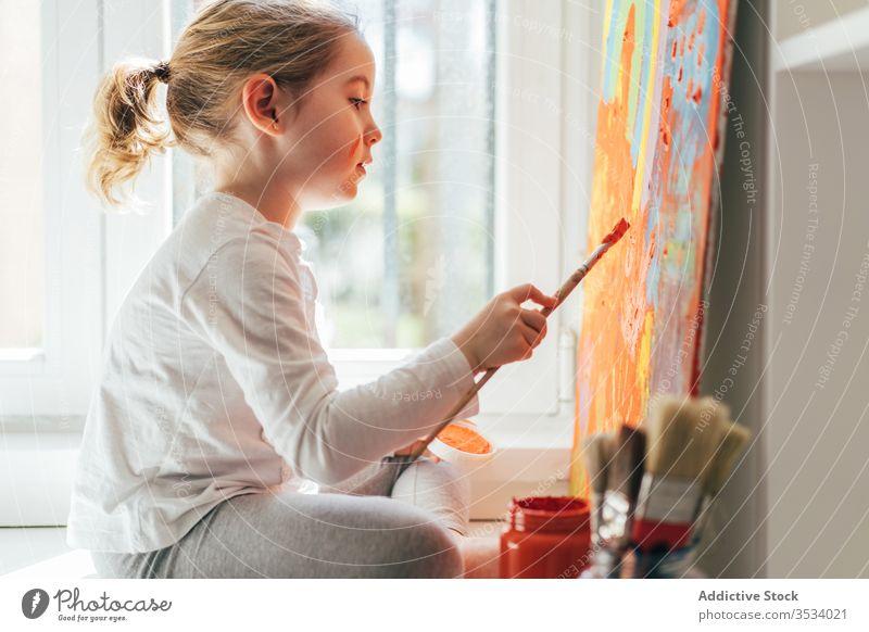Kleines Mädchen malt Bild mit Pinsel Leinwand zeichnen Farbe Pinselblume Regenbogen Malerei kreativ farbenfroh orange Fensterbrett lässig Kunst Hobby