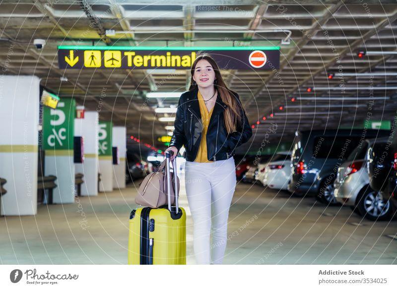Trendige weibliche Passagierin geht am Flughafenparkplatz entlang Frau Reisender Spaziergang Koffer führen Freude Gepäck parken Lächeln Tasche Ausflug warten