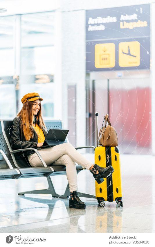 Frau mit eingeschaltetem Laptop im Wartebereich des Flughafens Tablette warten benutzend Verzögerung Browsen Passagier Gepäck Stil Abheben farbenfroh Surfen