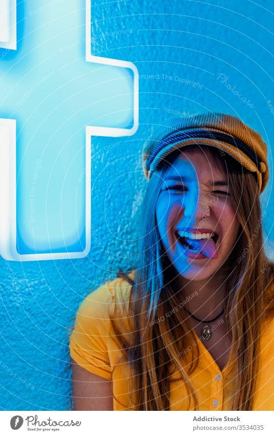 Junge fröhliche Frau mit lustigem Gesicht auf blauem Hintergrund Zunge zeigen neonfarbig auflehnen ausspannen Gesicht machen Spaß haben Grimasse Zeichen gelb