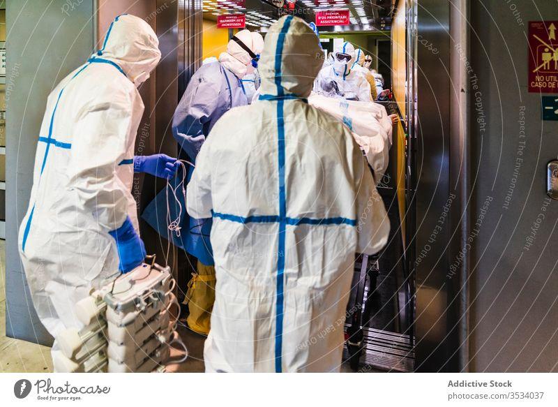 Gruppe von Ärzten in Schutzuniform bei der Entnahme des Patienten aus dem Aufzug Menschengruppe Arzt Klinik geduldig Uniform Fahrstuhl Krankenhaus