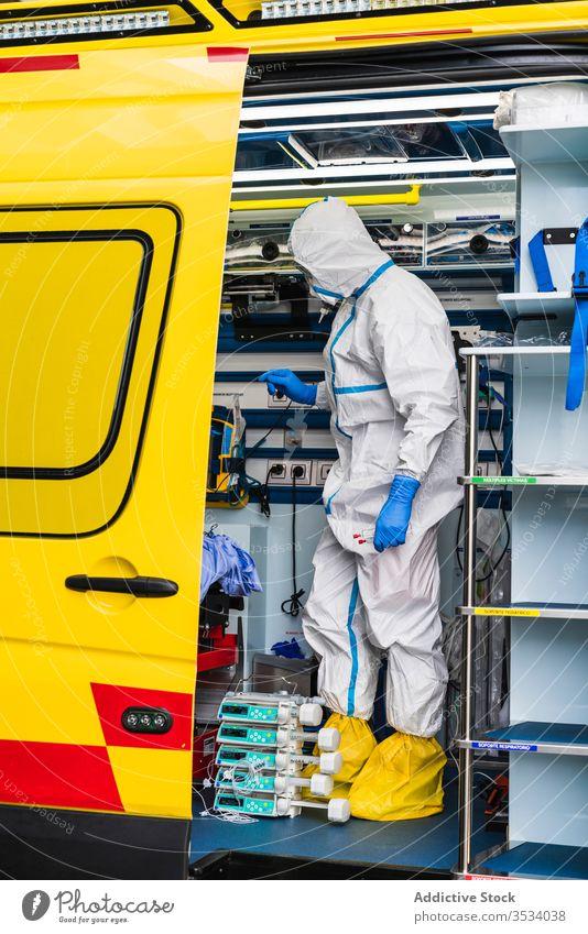 Arzt im Schutzanzug im Rettungswagen stehend PKW Tür Krankenwagen Gerät geduldig Virus Infektion untersuchen Uniform inspizieren Krankenhaus Dienst Fahrzeug