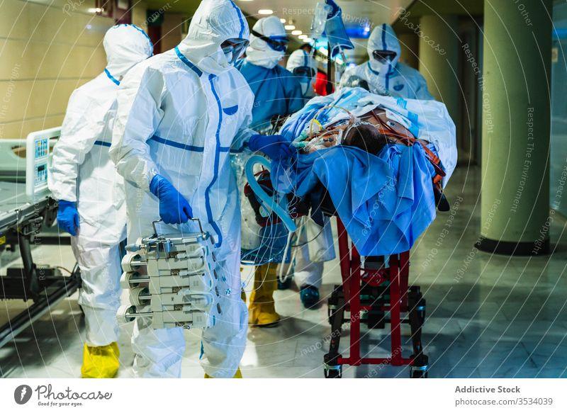 Eine Gruppe von Ärzten transportiert den Patienten in den Operationssaal Menschengruppe Arzt Krankenhaus geduldig viral Infektion Saal Klinik Uniform Mundschutz