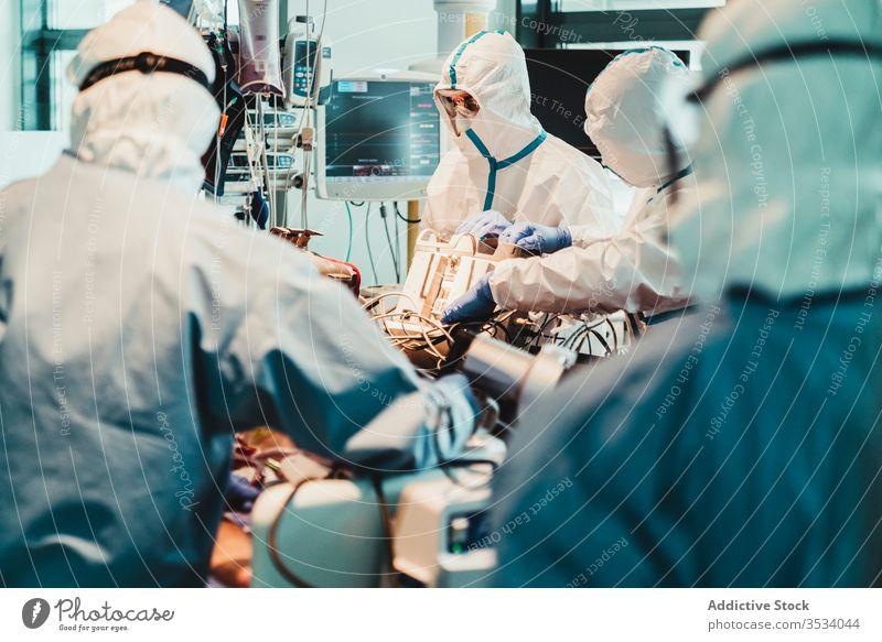Ärzte in Schutzuniform bei der Arbeit im Operationssaal eines Krankenhauses Arzt Klinik viral geduldig Pflege Infektion Gerät Leckerbissen Spezialist Mundschutz