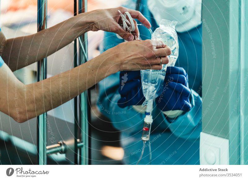 Anonyme mediale Krankenschwester hilft Arzt mit Flüssigkeit Krankenpfleger Klinik Mundschutz Tracht Uniform Krankenhaus Job Spezialist Leckerbissen Praktiker