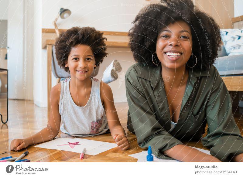 Mutter und Sohn zeichnen mit Buntstiften auf dem Boden. Spaß heimwärts Zeichnung Zusammensein Mama Schwarze Afroamerikaner gemischte Rassenfamilie