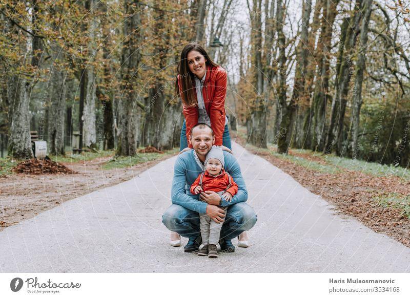 Glückliches Familien-Stil-Paar mit 1-jährigem Kind, das in rot-blauer Kleidung im Park lächelt schön Pflege Kaukasier heiter Kindheit Konzept niedlich Papa Papi