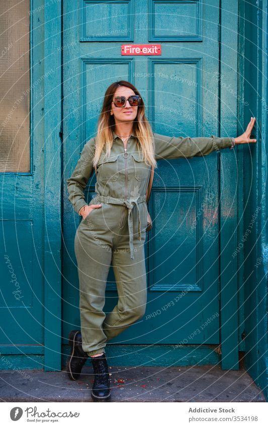 Fröhliche Frau mit Sonnenbrille steht in der Nähe der Notausgangstür trendy Türöffnung Stil heiter türkis farbenfroh hell gesamt Hand-in-Tasche Stiefel positiv