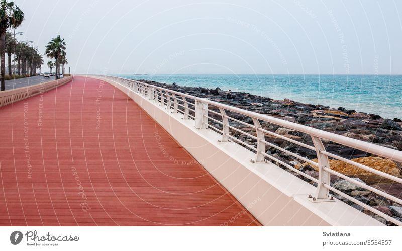 Wunderschöne Promenade mit Gehweg und weißem Zaun. Wellenbrecher Steine MEER Strand Blauer Himmel Landschaft Tourismus Wasser Küste Natur Meer reisen Urlaub