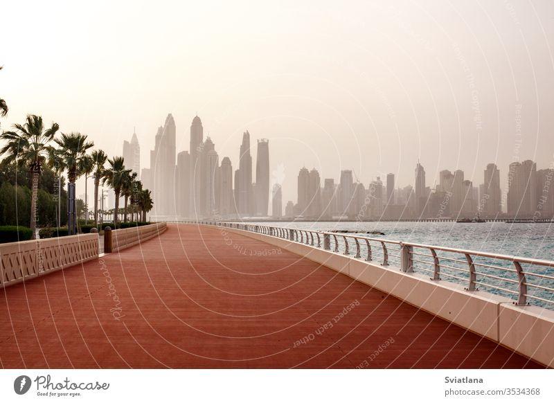Atemberaubende Aussicht auf die Wolkenkratzer in Dubai im Morgengrauen. VEREINIGTE ARABISCHE EMIRATE Wellenbrecher Steine MEER Strand Blauer Himmel Landschaft