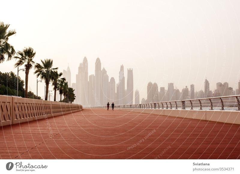 Morgens laufen ein Mann und eine Frau die Straße entlang, mit einem wunderschönen Blick auf Dubai. VEREINIGTE ARABISCHE EMIRATE Wellenbrecher Steine MEER Strand