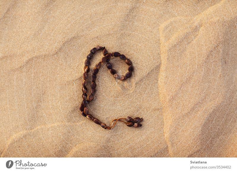 Rosenkranz auf dem Sand in der Wüste. Ramadan Kareem Daten arabisch Kultur Kaffee Lebensmittel Wasserkessel Tradition wüst Türkisch Sonne pho trinken uae Hunger