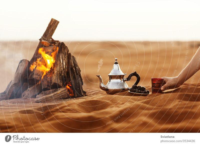 Datteln, Teekanne, Tasse mit Tee in der Nähe des Feuers in der Wüste mit einem schönen Hintergrund Daten Ramadan arabisch Kultur Kaffee Lebensmittel