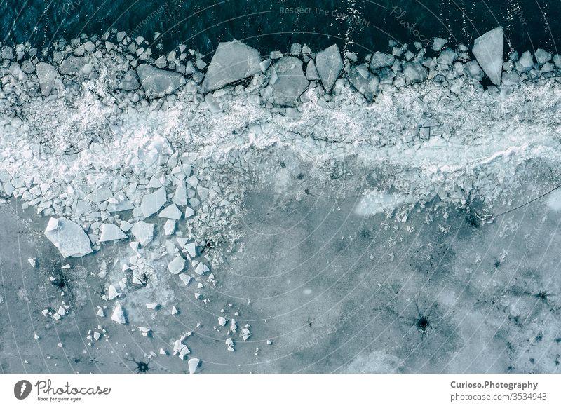 Gletscherlagune mit Eisbergen von oben. Luftaufnahme. Risse im Eis aus der Drohnenansicht. Konzept der Hintergrundtextur. blau Ansicht Wasser weiß Natur