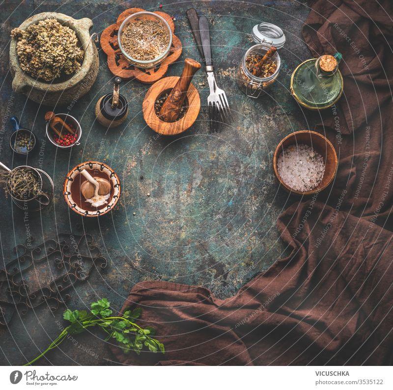 Rustikaler Hintergrund mit alten Küchenutensilien. Kräuter und Gewürze in Holzschüsseln, Olivenöl und Serviette. Rahmen. Ansicht von oben. rustikal