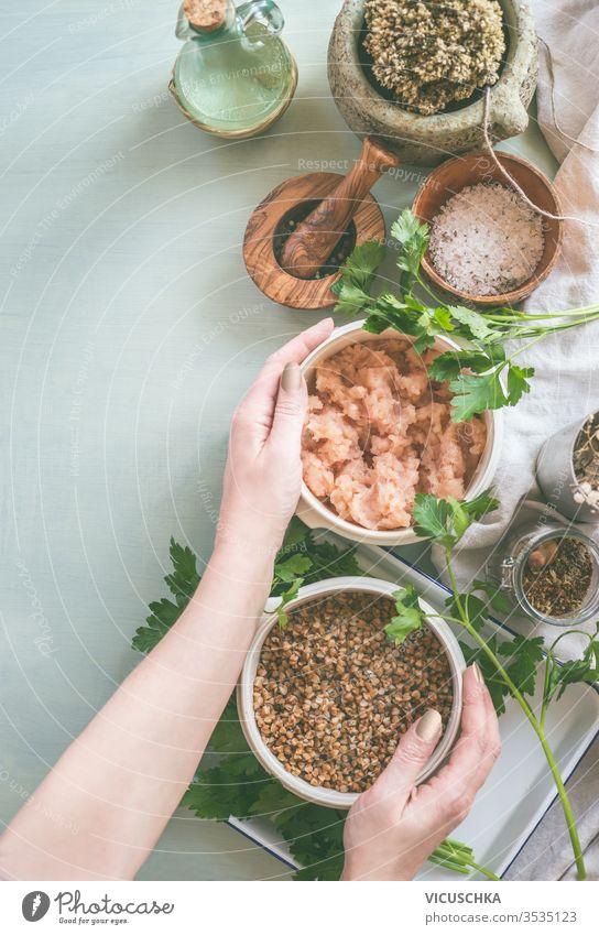 Frauenhände halten Schüsseln mit Zutaten für schmackhaftes Kochen. Ansicht von oben Essen zubereiten Vorbereitung Licht Küche Tische frisch Gewürz Beteiligung