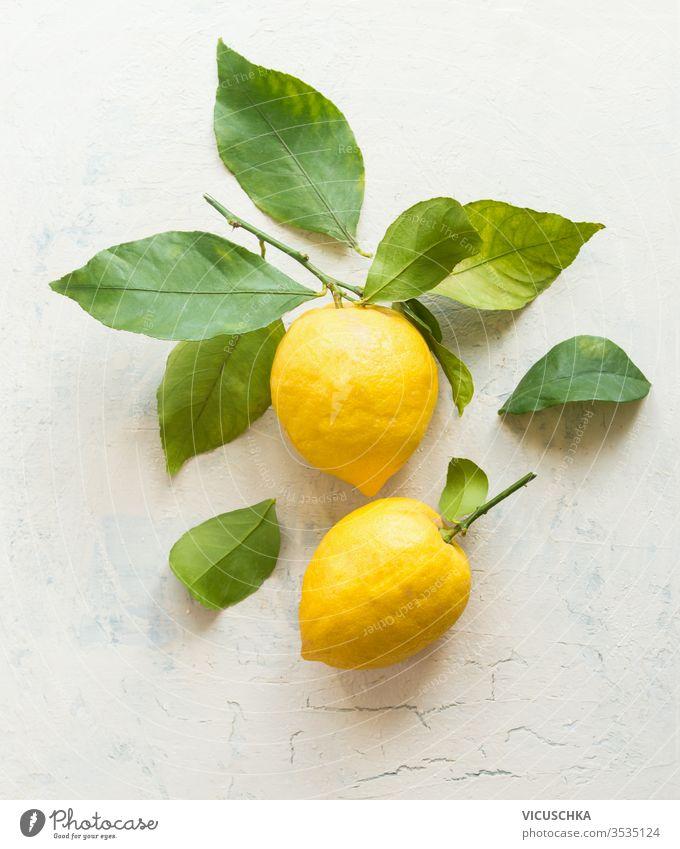 Reife Zitronen mit grüner Blattkomposition auf weißem Schreibtischhintergrund , Draufsicht. Organische Zitrusfrüchte. Flach gelegt. Konzept für gesunde Ernährung.