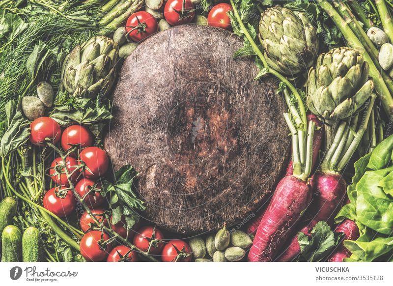 Verschiedene Gemüse um eine alte Holzplatte herum. Ansicht von oben. Rahmen aus Bio-Gemüse. Konzept für gesundes, sauberes Essen verschiedene altehrwürdig