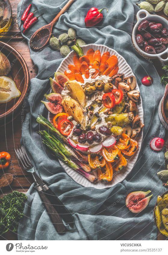 Veganer Hummus-Partyteller mit gebratenem, gegrilltem, frischem und eingelegtem Gemüse . Ansicht von oben. Gesunde Ernährung. Zwischenmahlzeit. Mediterrane Küche.