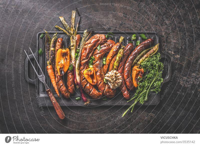 Verschiedene gegrillte Fleischwürste mit gebratenem Gemüse auf gusseiserner Grillpfanne mit Fleischgabel auf dunklem, rustikalem Hintergrund. Grillfest Oktoberfest deutsche Küche. Ansicht von oben. Traditionelle Küche