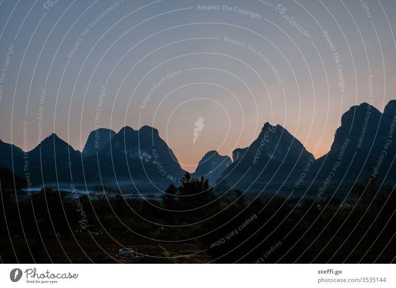Aussicht auf Bergkette mit Nebel in der Abenddämmerung in Yangshuo, Guilin China Asien Guilinberge Karst Karstlandschaft Karstberge Gebirge gebirgskette