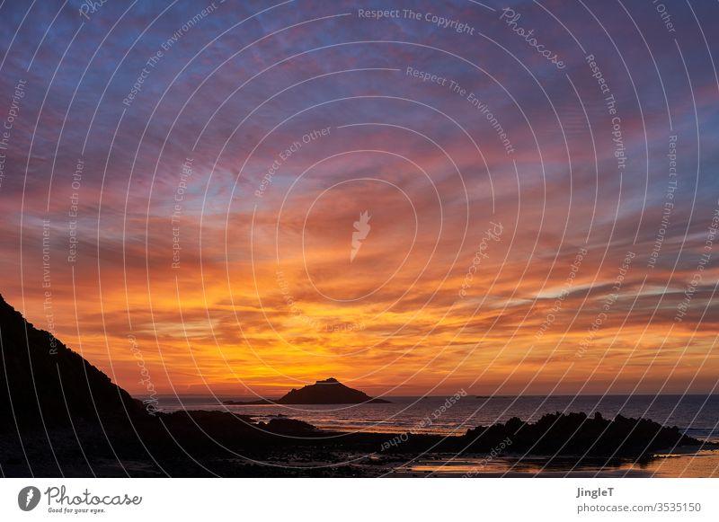 Abendrot im teilweise wolkigen Himmel an einer felsigen Küste am Atlantik Felsen Wolken Stimmung blau gold schwarz Horizont Insel Silhouette warm Außenaufnahme