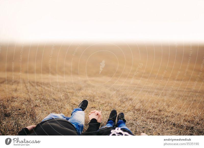 Verliebtes Ehepaar, Mann und Frau liegen im Feld und halten sich an den Händen. Begriff der Liebe. Herbstliche Stimmung. Ort für die Inschrift Menschen Sommer