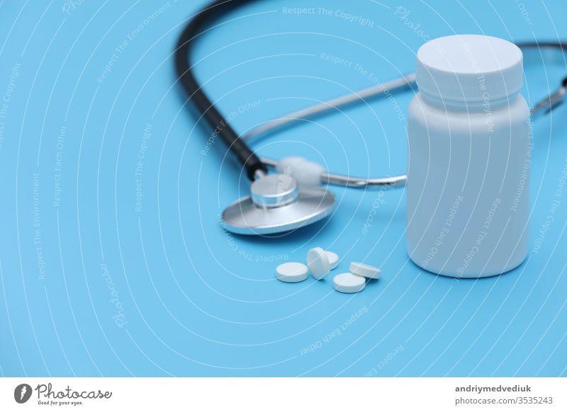Aus der Pillenflasche austretende Pillen Spritzenthermometer und Stethoskop auf blauem Hintergrund. selektiver Fokus. Tablette Thermometer covid-19 Coronavirus