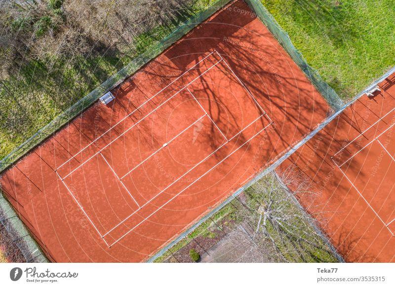 ein Tennisplatz von oben Sport Tennisplätze Asche orange weiß Linien Sonne Schatten Sommer Winter stechend Tennisnetz Tennisnetze Ball Bälle Tennisball Bäume