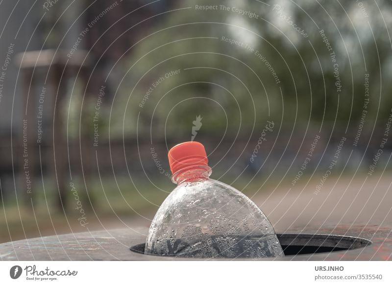 eine leere PET Flasche mit orangefarbenem Schraubverschluss wird im Papierkorb entsorgt Polyethylenterephthalat Flaschenhals wegwerfen weggeworfen Müll