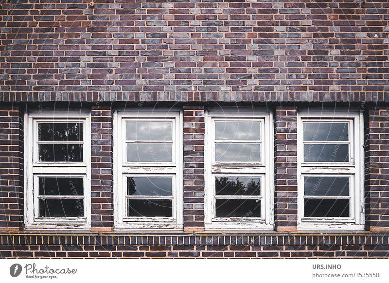 alte abgeblätterte Sprossenfenster in einer Klinkerfasade geometrisch symetrisch Geometrie Architektur Symetrie Fasade Holzfenster abgeblätterte Farbe Fenster