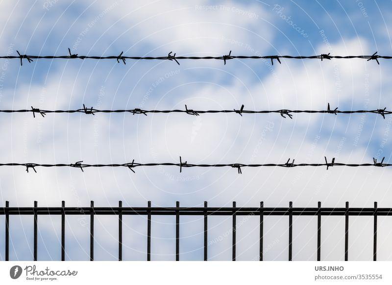 Stacheldraht über einem Zaun vor Schönwetterwolken Drahtzaun Wolken schönes Wetter abgesperrt absperren undurchlässig kein Durchgang wolkig Sperrdraht