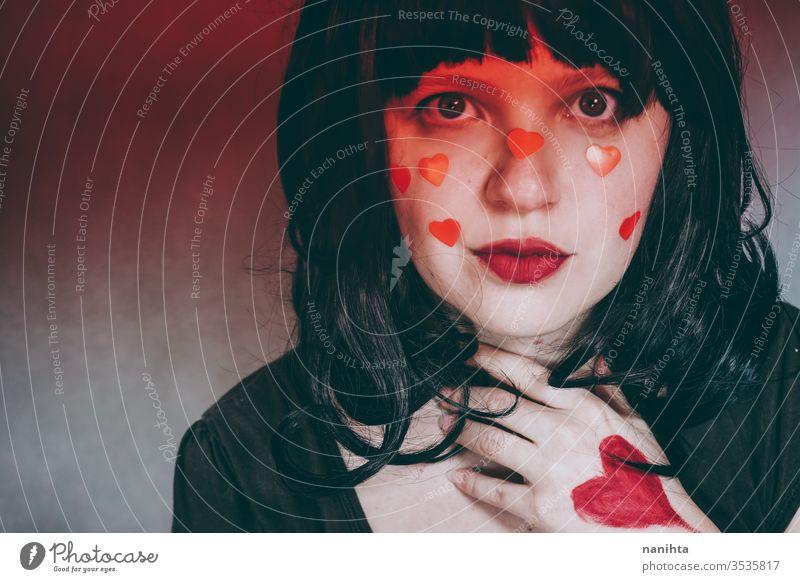 Künstlerisches Porträt einer jungen Frau mit rotem Herz-Make-up und bedeckt von einem roten Farbverlauf Liebe Schönheit hübsch Gesicht Kunst künstlerisch