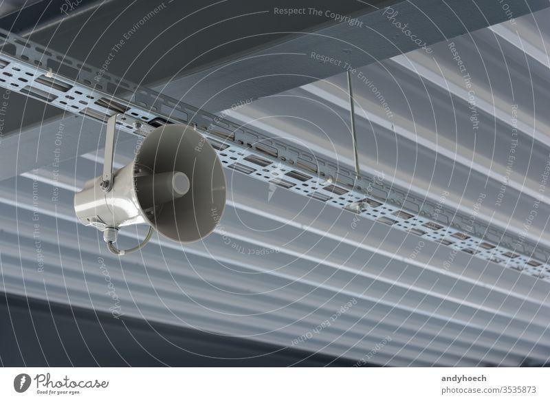 Ein grauer Sprecher hängt von der modernen Decke ab abstrakt wach ankündigen Ankündigung Architektur Kunst Audio Hintergrund Ausstrahlung Gebäude