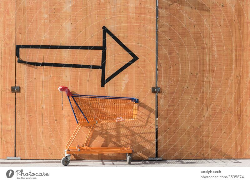 Mit dem Einkaufswagen immer auf dem Pfeil nach der Einkaufstour Aktion Hintergrund Vorteile kaufen Wahl Mitteilung Konzept Verbraucher Konsumverhalten