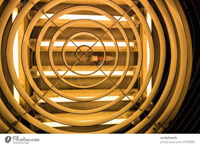 Eine alte Glühbirne in der Mitte von Leuchtstoffröhren abstrakt Kunst Hintergrund Hintergründe gebaute Struktur Zimmerdecke Deckenlampe kreisen kreativ