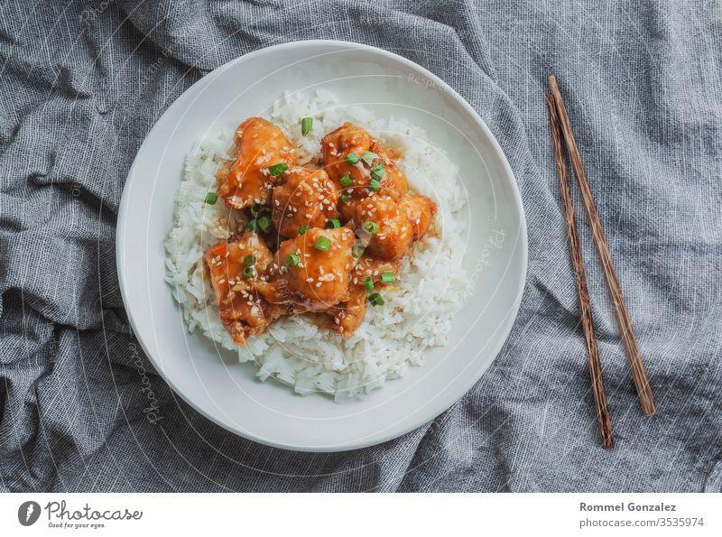 Köstliches Hühnerfleisch mit süßsaurer Orangensauce und Jasminreis nach chinesischer Art, Draufsicht. Kochen Schalen & Schüsseln Tisch Peperoni Hähnchen orange