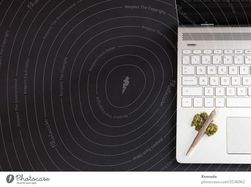 Marihuana und technologischer Hintergrund. Cannabis-Knospen und Marihuana-Gemisch auf Laptop isoliert auf schwarzem Hintergrund mit Kopierraum links.
