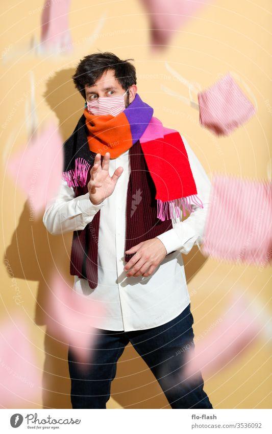 Ein vorsichtiger Kerl mit Mundschutz grüßt vorsichtig Lifestyle kaufen Stil Design schön Gesicht Allergie Berufsausbildung Azubi Studium Handel Medienbranche