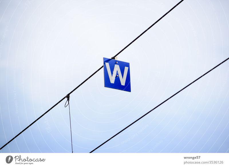 Ein weißes W auf blauer Tafel hängend an einem Drahtseil Buchstabe Schild Schilder & Markierungen Außenaufnahme Menschenleer Farbfoto Schriftzeichen Buchstaben