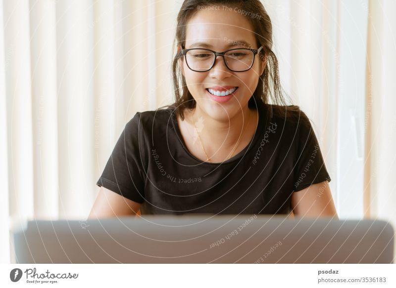 glückliche Frau mit Laptop. Junge asiatische Frau sitzt zu Hause und arbeitet am Laptop attraktiv offen lässig heiter Kaffeehaus Computer Tagung lockig