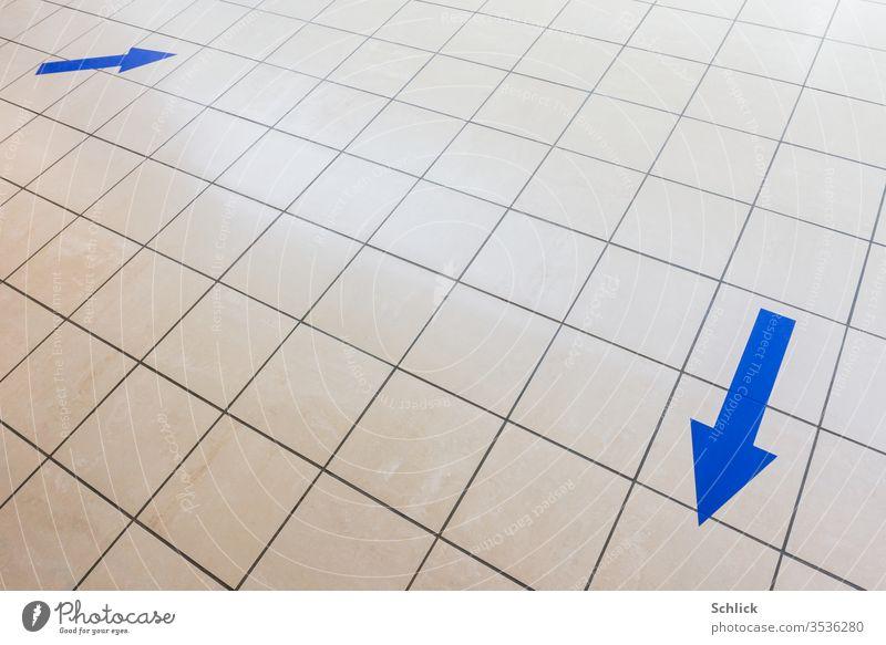 Coronakrise zwei blaue Pfeile auf hellen Kacheln zeigen auf dem Boden in verschiedene Richtungen grau hellgrau Wegweiser covid-19 Einkaufen Bodenfliesen