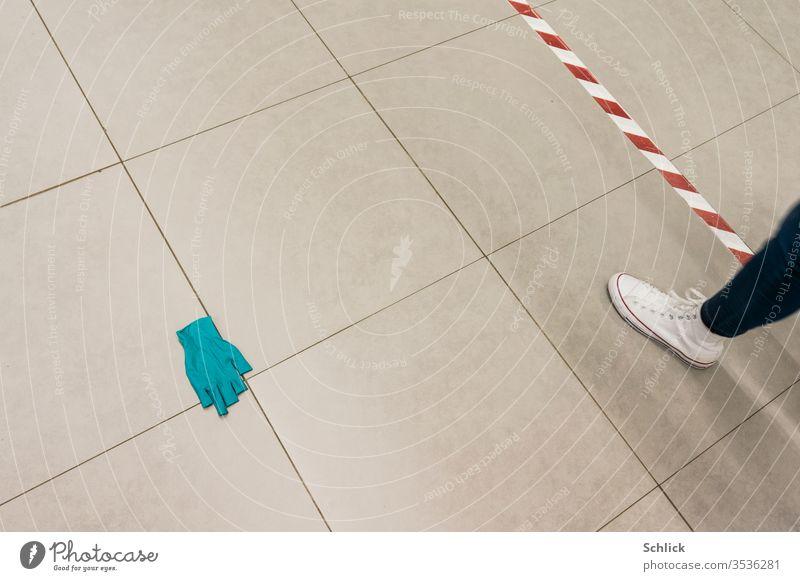 Coronakrise gekachelter Boden mit wegeworfenem Einweghandschuh Abstandsmarkierung und Bein eines Passanten Kacheln liegen wegwerfen Markierung Markierungsband