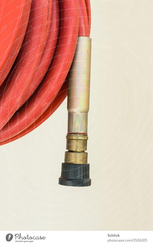 Da hängt des Ende des Feuerlöschschlauches voller Erwartung auf das nächste Feuer tatenlos nach unten Schlauch Brandbekämpfung Detail aufgerollt rot schwarz